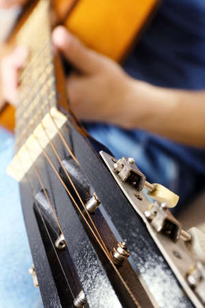 hand jamming: Young man playing on acoustic guitar close up