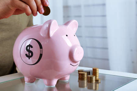 put: Man put coin into a piggy-bank Stock Photo