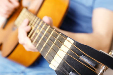 jamming: Young man playing on acoustic guitar close up
