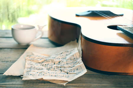 Acoustic guitar and cup of tea next the window with rain drops Stock Photo