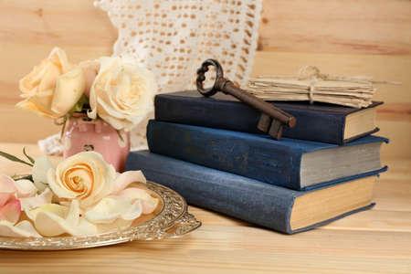 Frische Rosen mit alten Buch, Schlüssel und Buchstaben auf Holztisch Hintergrund. Vintage-Konzept