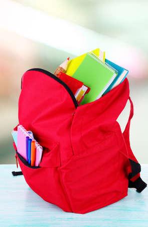 Rode tas met schoolspullen op houten tafel in de klas Stockfoto