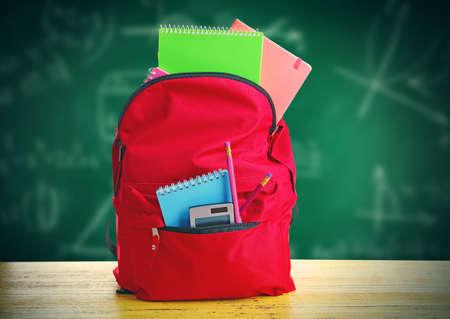Borsa rossa con attrezzature scolastiche sulla tavola di legno, vicino alla lavagna