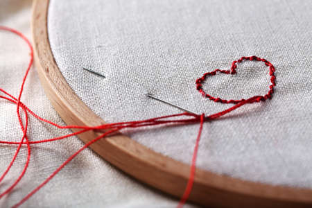 thread count: The embroidery hoop with canvas and red sewing threads on table close up
