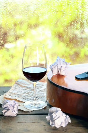 Acoustic guitar and glass of wine next the window with rain drops Stock Photo