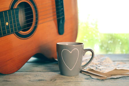 next stage: Acoustic guitar and cup of tea next the window with rain drops Stock Photo