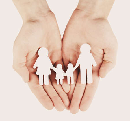 children hands: Female hands with family model on light background, close-up