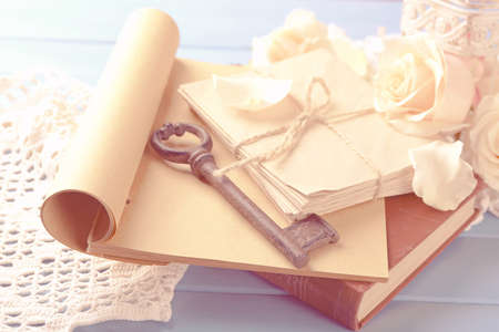 Fresh roses with old book and letters on color wooden table background. Vintage concept Stockfoto