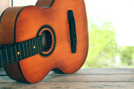 Acoustic guitar next the window with rain drops