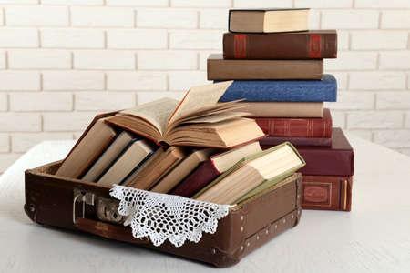 libros abiertos: Montón de libros viejos en el fondo de la pared de ladrillo