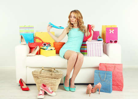 Woman with shopping bags and shoes on sofa in room Stock Photo