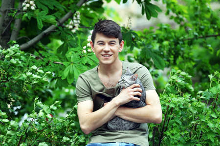 Handsome young man with cute cat outdoors