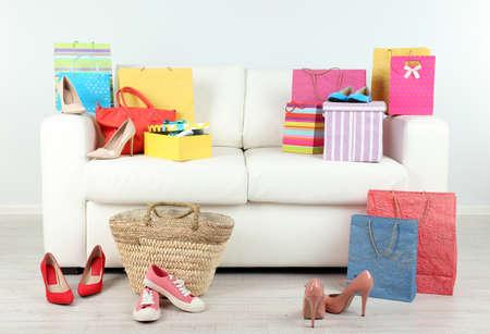 Montón de bolsas con cajas y zapatos en el sofá en la habitación Foto de archivo