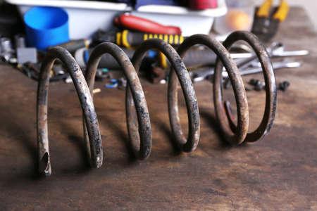 metal spring: Large metal spring on workplace in garage Stock Photo