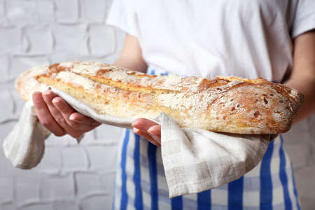 holding close: Woman holding tasty fresh bread, close up