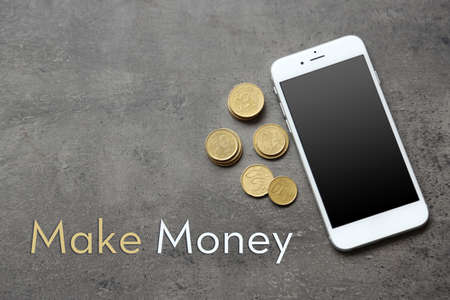 hp: Smart phone with euro banknote and coins on grey background. Stock Photo