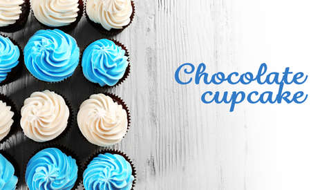 birthday cupcake: Tasty colourful cupcakes in a row on white wooden  background