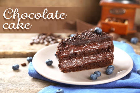 cake plate: Chocolate cake with chocolate cream and fresh blueberries on plate, on wooden background