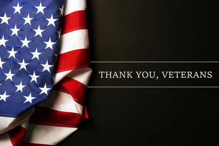 Text Thank A You, Veterans on black background near American flag