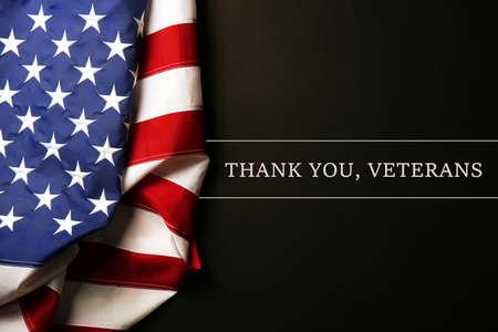 Tekst Dank A U, veteranen op een zwarte achtergrond in de buurt van de Amerikaanse vlag Stockfoto