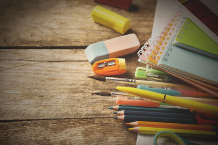 book background: Bright school stationery on old wooden table Stock Photo