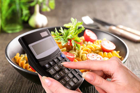 Calculator in hand on delicious macaroni dish background