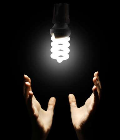 overuse: Hands with energy saving light bulb on black background Stock Photo
