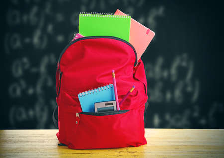 Red bag with school equipment on wooden table, near blackboard