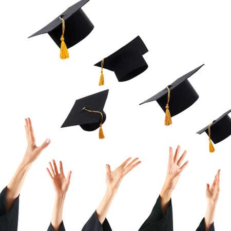 fondo de graduacion: Graduados que lanzan los sombreros de graduaci�n de manos, aislado en blanco Foto de archivo