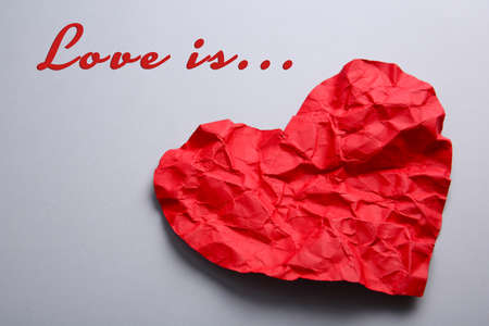table scraps: Crumpled paper heart on gray background Stock Photo