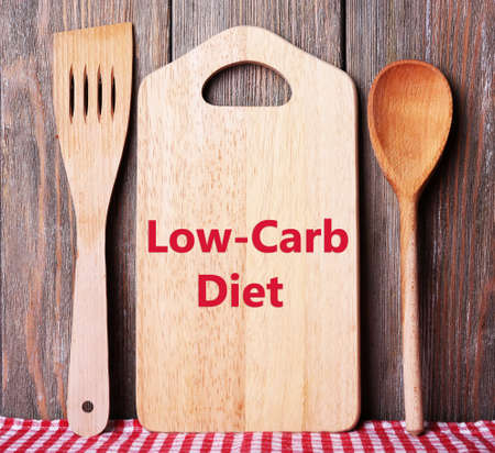 frame less: Text Low-Carb Diet on cutting board on wooden planks background