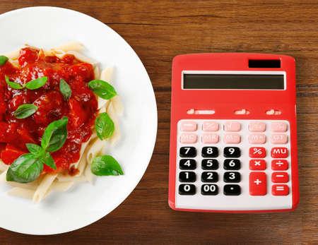 Calcolatore e pasta deliziosa con salsa di pomodoro su priorità bassa di legno Archivio Fotografico