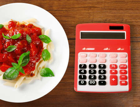 Calculator and delicious pasta with tomato sauce on wooden background Stock Photo