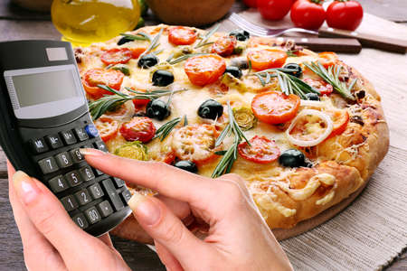 Calculator in hand on delicious pizza background
