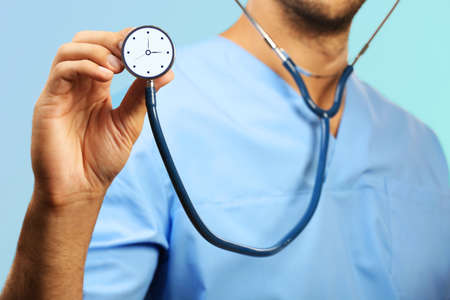 ultimatum: Male doctor holding stethoscope with clock
