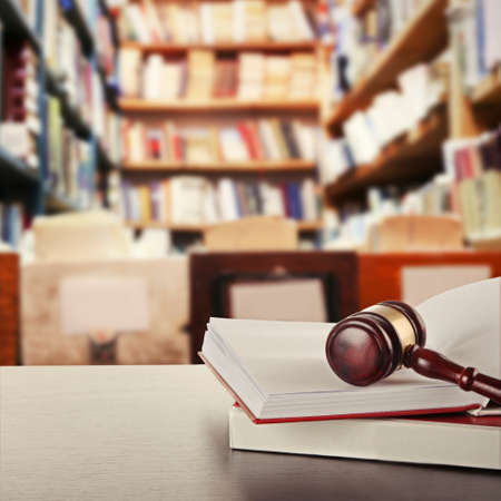 law book: Wooden judges gavel lying on law book on table in library