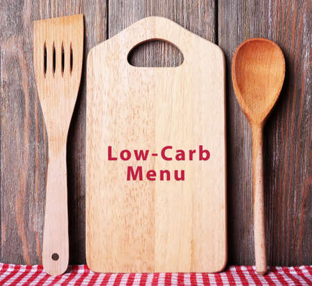frame less: Cutting board with text Low-Carb Menu on wooden planks background