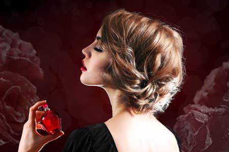 Giovane e bella donna con la bottiglia di profumo sul fiore sfondo scuro
