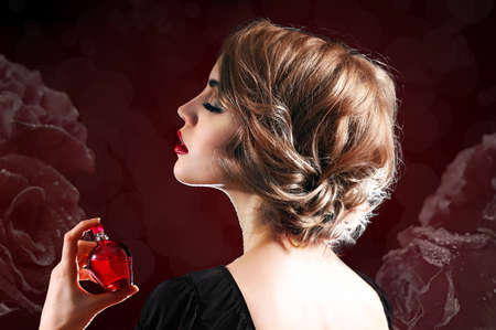 Beautiful young woman with perfume bottle on dark flower background Stockfoto