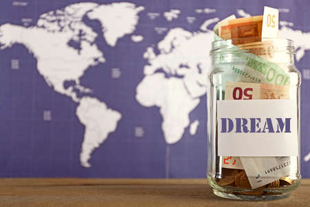 meanness: Savings for trip in glass bank on colourful map background
