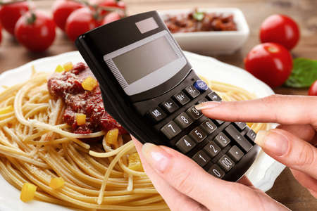 Calculadora en mano sobre fondo deliciosa macarrones plato Foto de archivo
