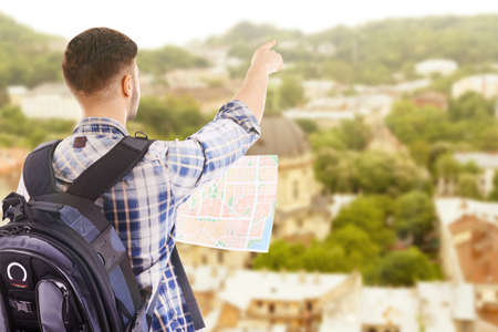 guid: Traveler with map on cityscape background