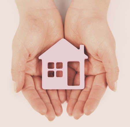 color model: Female hands with model of house on light background Stock Photo