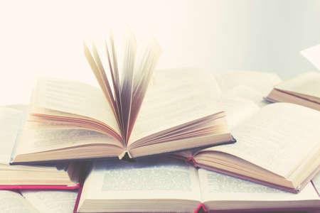 Molti libri aperti su sfondo chiaro