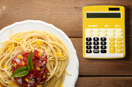 Calculator and delicious spaghetti with tomato sauce on wooden background