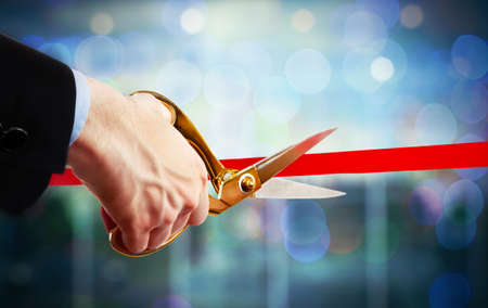 new beginning: Businessman cutting red ribbon with pair of scissors close up