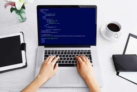 ノート パソコン、ノート パソコンでプログラミング コードの記述をしている女の人 写真素材