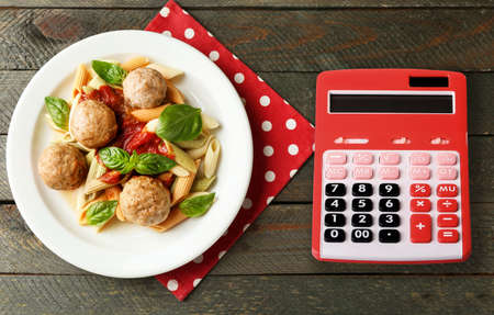 Calculator and delicious pasta with meatballs on wooden background