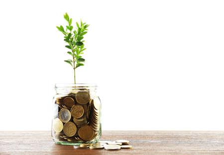 Geld met het kweken van spruit in glazen pot op tafel geïsoleerd op wit Stockfoto