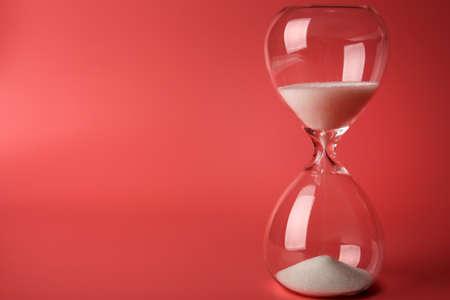 Reloj de arena en el fondo de color rosa